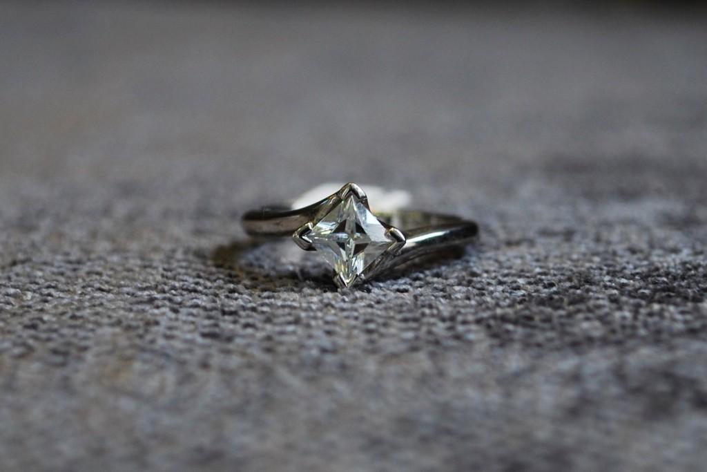 Twist style princess cut diamond solitaire engagement ring